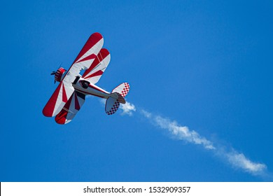 red and white biplane with smoke