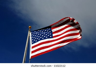Red, white and blue American flag flies against a vivid blue sky with white cloud cover.