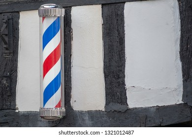 red white and blue barbers pole on ancient timber wall in the UK