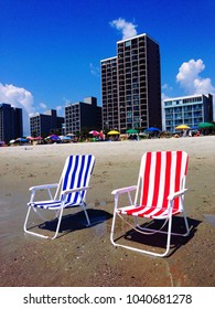 Red, white & blue beach chairs on the beach.