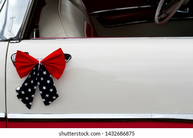 A red, white and blue bow is attached to a vintage door handle on a classic car.  There is copy space for you to write your message in the white area of the door.
