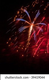Red, white and blue burst of fireworks amid falling embers and red smoke