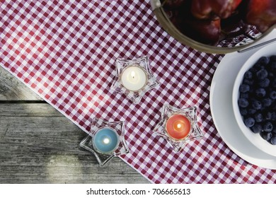 Red, white, and blue candle stars on an outdoor picnic table with apples and blueberries on a checkered blanket