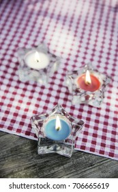 Red, white, and blue candle stars on an outdoor picnic table with checkered blanket