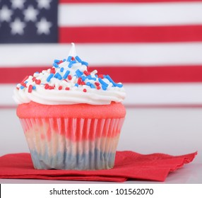 Red white and blue cupcake with american flag in background