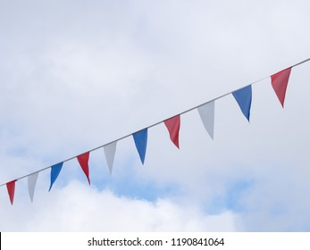 Red, white and blue festive bunting flags against sky background. Triangle shapes.