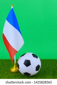 Red white and blue flag of France on green grass with a soccer ball on a green screen. Vertical image, copy space.