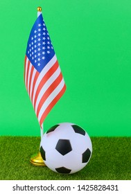 Red white and blue flag of the United States on green grass with a soccer ball on a green screen. Vertical image, copy space.