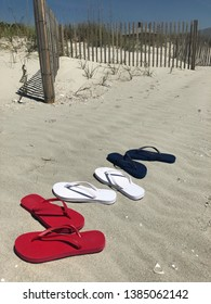 Red white and blue flip flops sitting the sand at the beach.