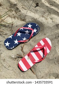 Red white and blue flip flops sitting in the sand.