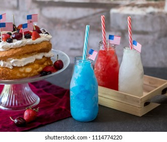 Red white and blue frozen drinks and  patriotic angel food cake with blueberries cherries and strawberries.  Happy 4th of july