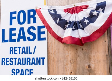 Red, White and Blue Patriotic Banner on Wooden Fence with For Lease Sign Depicting Failing Economic Times