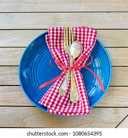 Red White and Blue Picnic Table Place Setting with napkin, fork, spoon and plate.  Square and flat layout style photo taken outside with reflections of trees and warm sunlight in the silverware.