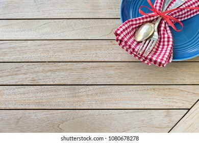 A Red White and Blue Picnic Table Place Setting with napkin, fork and spoon and plate in an upper corner on horizontal  wood board table top background with room or space for copy, text or your words.