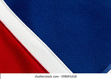 Red, white and blue polyester fabric of a hockey jersey, close up