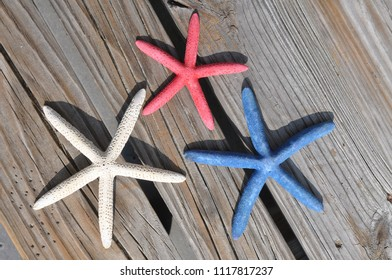Red, white and blue star fish sitting on weathered wood.
