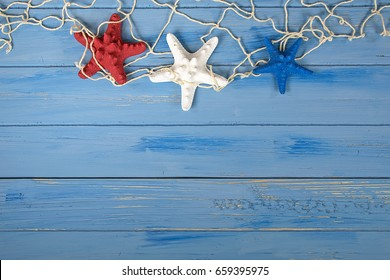 red white and blue starfish in nautical netting on blue rustic wood