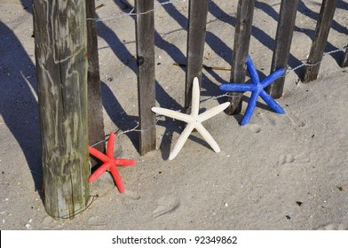 Red, White and Blue Starfish sitting by beach fence. Room for your text