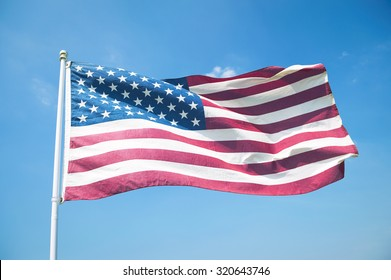 The red, white, and blue stars and stripes of an American flag waving in bright blue sky