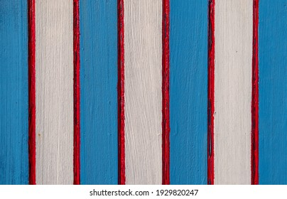 Red, white and blue stripes painted on old wood background.