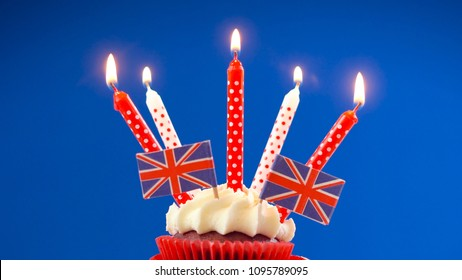 Red white and blue theme cupcakes and cake stand with UK Union Jack flags for Queen's Birthday weekend celebration or Great Britain party food.
