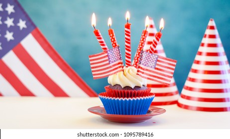 Red white and blue theme cupcakes with USA flags for Independance Day or USA theme party food.