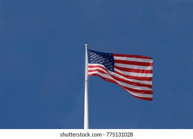 A red, white and blue United States flag waving against a blue sky.