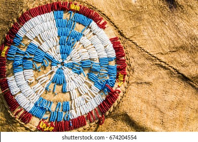 Red, white, blue and yellow Native American beads are sewn in a cross pattern on a buffalo hide