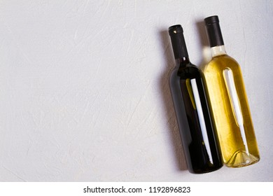 Red and white bottles of wine on white stone texture background. View from above, top studio shot