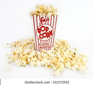 Red and white box of overflowing popcorn with kernels at the base of the box. Horizontal.