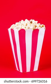 Red and white box of popcorn isolated on red background
