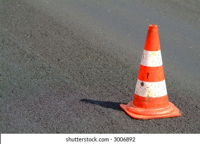 a red white brindled traffic cone on street