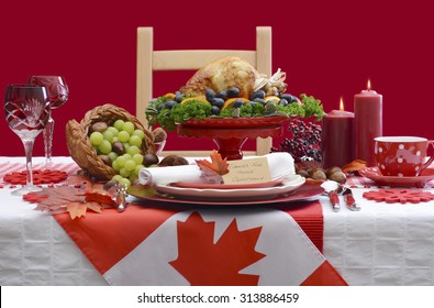 Red and white Canadian theme Thanksgiving Table setting with flag and Roast Turkey Chicken on large platter centerpiece .