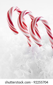 Red and white candy canes surrounded by faux snowflakes against a white background.