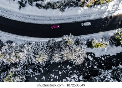 red and white cars driving on asphalt road along the mountain river. Drone view of frozen winter forest
