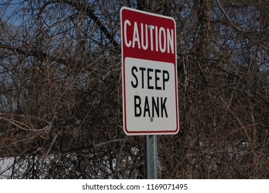 A red and white caution steep bank sign