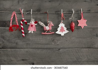 Red white checked christmas decoration hanging on an old wooden wall background.
