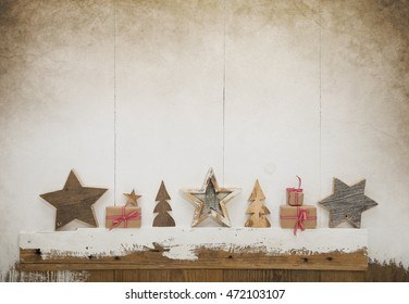 Red white checked christmas gifts with handmade carved wooden stars on old wooden background for decoration.