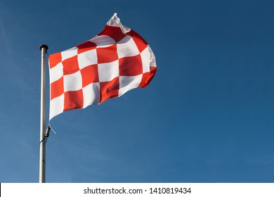 Red and white checkered flag of North Brabant the southern part of the Netherlands waving on a blue sky
