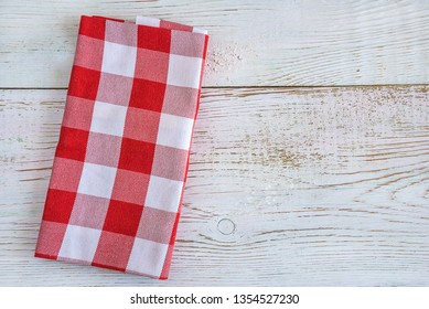 Red and white checkered napkin on the rustic white paint wooden background top view with copy space