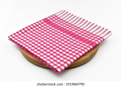 Red and white checkered napkin on round wooden board, isolated on white background