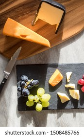 Red and white cheese flat lay food image with grapes on rustic kitchen table. Served on wood board and slate coaster with cheese knife.