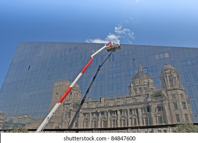 A Red and White Cherry Picker and Glass Building with Reflection of Historic Building