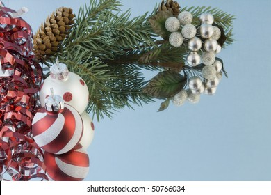 red and white Christmas baubles with ribbon, fir branch, reflections and copy space