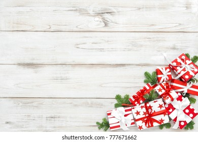 Red white Christmas decoration and pine tree branches on wooden background. Holidays banner.