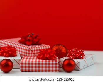 Red and white Christmas and New Year gift boxes and Christmas ornaments on white table and red background with and copy space for text, festive and celebration concept