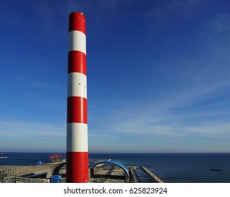red and white coal fired power plant stack with blue sky