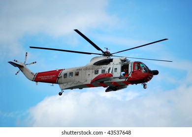 The red and white coastguard helicopter in flight, against a blue summer sky.