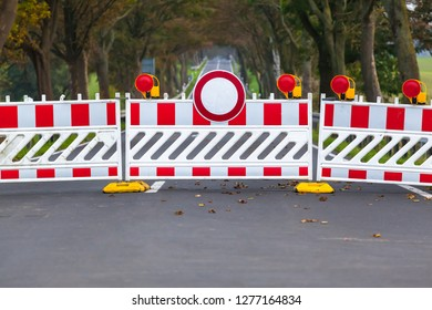 Red and white colored street barrier on closed avenue road at countryside, grey asphalt copy space background