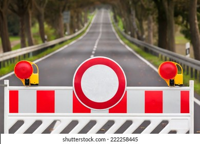 Red and white colored street barrier at an empty road/Closed Road